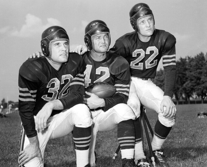 FILE - In this Aug. 25, 1948, file photo, veteran quarterback Sid Luckman, center, poses with two newcomers to the Chicago Bears, Johnny Lujack, left, and, Bobby Layne, during preseason football workouts at Collegeville, Ind. Helmets have evolved from the original hard leather of the NFL's infancy to hard polycarbonate single-piece shells with various amounts of padding and air bladders that served as the primary form of head protection into the beginning of this century.  (AP Photo/File)