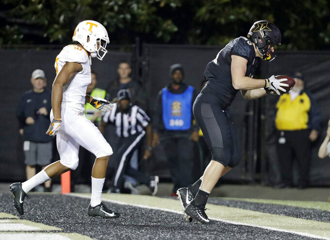 Vanderbilt tight end Cody Markel, right, catches a 2-yard touchdown pass ahead of Tennessee defensive back Nigel Warrior, left, in the second half of an NCAA college football game Saturday, Nov. 24, 2018, in Nashville, Tenn. (AP Photo/Mark Humphrey)