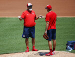 Washington Nationals' pitching coach Paul Menhart, left, talks with pitcher Daniel Hudson on the mound during a baseball training camp workout at Nationals Stadium, Sunday, July 5, 2020, in Washington. (AP Photo/Carolyn Kaster)