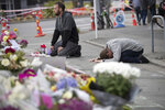 FILE - In this March 19, 2019, file photo, mourners pray near the Linwood mosque in Christchurch, New Zealand. More than 60 survivors and family members will confront the New Zealand mosque gunman during the four-day sentencing starting Monday, Aug. 24, 2020. Twenty-nine-year-old Australian Brenton Harrison Tarrant has pleaded guilty to 51 counts of murder, 40 counts of attempted murder and one count of terrorism in the worst atrocity in the nation's modern history.(AP Photo/Vincent Thian, File)