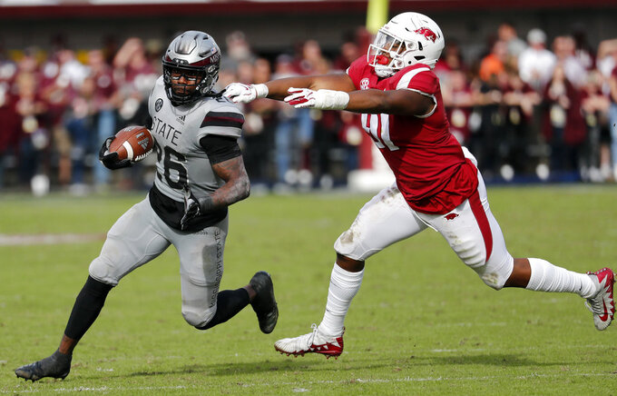 Arkansas quarterback Ty Storey (4) fumbles the ball after being double teamed by Arkansas defensive back Jayden Minchew (38) and defensive lineman Randy Ramsey (10) during the first half of an NCAA college football game in Starkville, Miss., Saturday, Nov. 17, 2018. Mississippi State won 52-6. (AP Photo/Rogelio V. Solis)