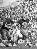 FILE - In this 1924 file photo, Illinois' Red Grange, left, follows a blocker on a 95-yard kickoff return for a touchdown against Michigan. When University of Illinois star Red Grange joined the NFL in 1925, a deal scandalously planned while he was still playing in college, he drew scorn from those in college football. Not only was professional football considered barbarian, it was thought to be a lesser version of the sport (AP Photo/File)