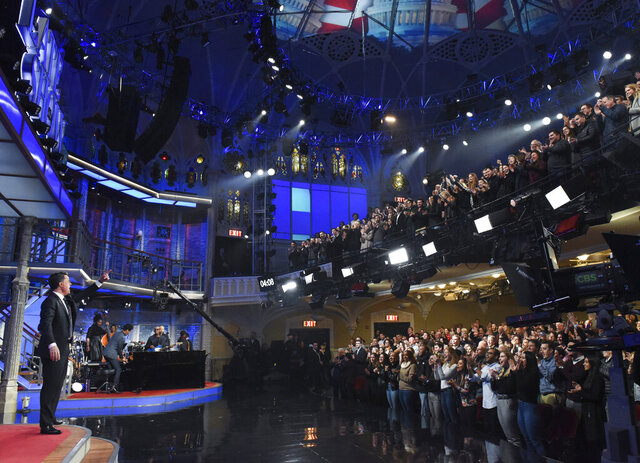 This Feb. 4, 2020 image released by CBS shows host Stephen Colbert, left, greeting the audience during a taping of
