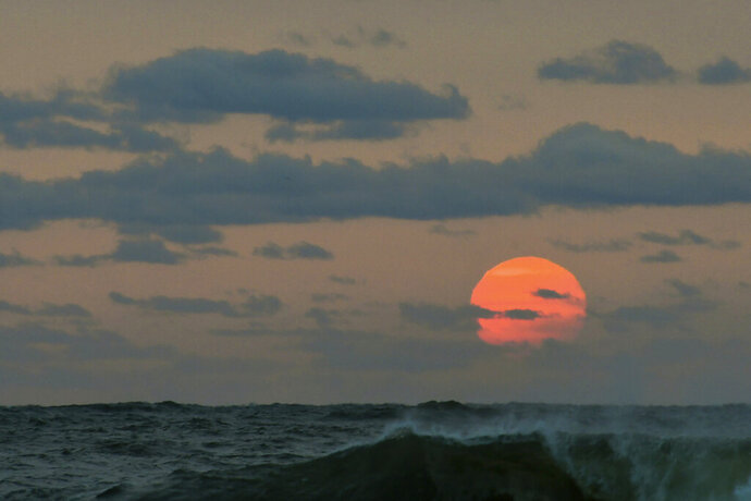 This photo taken at sunrise from Surf City on Long Beach Island in New Jersey shows the sun shrouded in smoke and brown haze Tuesday, Sept. 15, 2020. The smoke from dozens of wildfires in the western United States is stretching clear across the country — and even pushing into Mexico, Canada and Europe. While the dangerous plumes are forcing people inside along the West Coast, residents thousands of miles away in the East are seeing unusually hazy skies and remarkable sunsets. (Elizabeth Laird via AP)