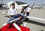 Air Race1 CEO, Jeff Zaltman, left, poses with his colleagues next to their electric aircraft during the opening day of Dubai Airshow in Dubai, United Arab Emirates, Sunday, Nov. 17, 2019. The biennial Dubai Airshow has opened as major Gulf airlines reign back big-ticket purchases after a staggering $140 billion in new orders were announced at the 2013 show before global oil prices collapsed. (AP Photo/Kamran Jebreili)