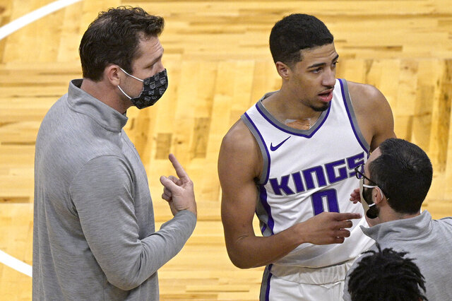 Sacramento Kings coach Luke Walton, left, talks to guard Tyrese Haliburton (0) during a timeout in the second half of the team's NBA basketball game against the Orlando Magic, Wednesday, Jan. 27, 2021, in Orlando, Fla. (AP Photo/Phelan M. Ebenhack)
