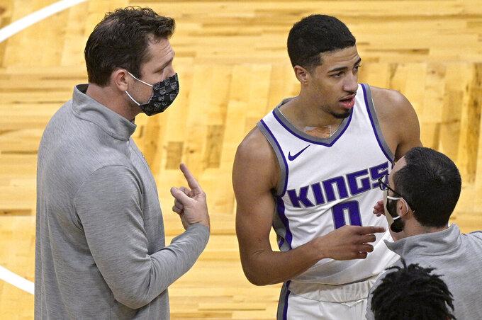 Sacramento Kings coach Luke Walton, left, talks to guard Tyrese Haliburton (0) during a timeout in the second half of the team's NBA basketball game against the Orlando Magic, Wednesday, Jan. 27, 2021, in Orlando, Fla. (AP Photo/Phelan M. Ebenhack)