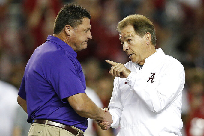 "FILE - In this Nov. 4, 2017, file photo, LSU head coach Ed Orgeron, left, and Alabama head coach Nick Saban meet in the center of the field before an NCAA college football game, in Tuscaloosa, Ala. Eight SEC games have been postponed already with only Arkansas, Kentucky and South Carolina not affected _ yet. ""I do believe that Alabama and LSU ought to play this year, and I do believe we're going to play somehow, some way,"" Orgeron said. (AP Photo/Brynn Anderson, File)"