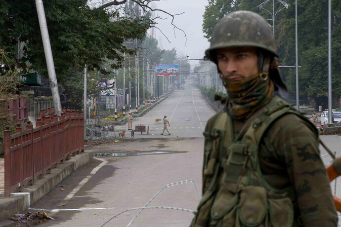 Indian paramilitary soldier stands guard on a deserted road leading towards Independence Day parade venue during lockdown in Srinagar, Indian controlled Kashmir, Thursday, Aug. 15, 2019.Indian Prime Minister Narendra Modi says that stripping the disputed Kashmir region of its statehood and special constitutional provisions has helped unify the country. Modi gave the annual Independence Day address from the historic Red Fort in New Delhi as an unprecedented security lockdown kept people in Indian-administered Kashmir indoors for an eleventh day. (AP Photo/ Dar Yasin)