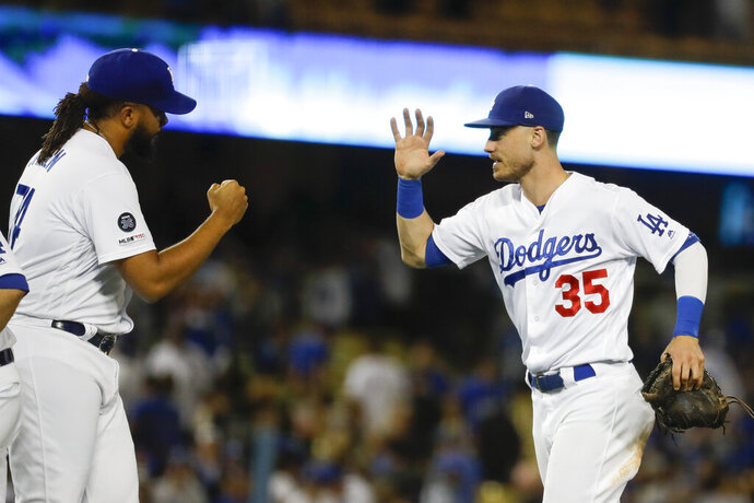Los Angeles Dodgers right fielder Cody Bellinger, right, celebrates after their 7-5 win against the Tampa Bay Rays with relief pitcher Kenley Jansen after a baseball game in Los Angeles, Tuesday, Sept. 17, 2019. (AP Photo/Chris Carlson)