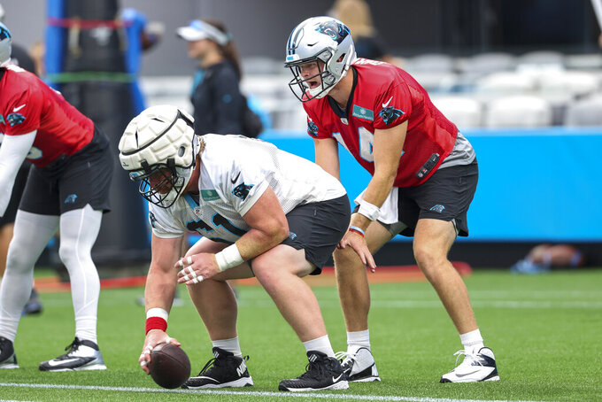 Carolina Panthers quarterback Sam Darnold, right, takes the snap from center Matt Paradis during a Fan Fest practice at the NFL football team's training camp in Charlotte, N.C., Friday, Aug. 6, 2021. (AP Photo/Nell Redmond)