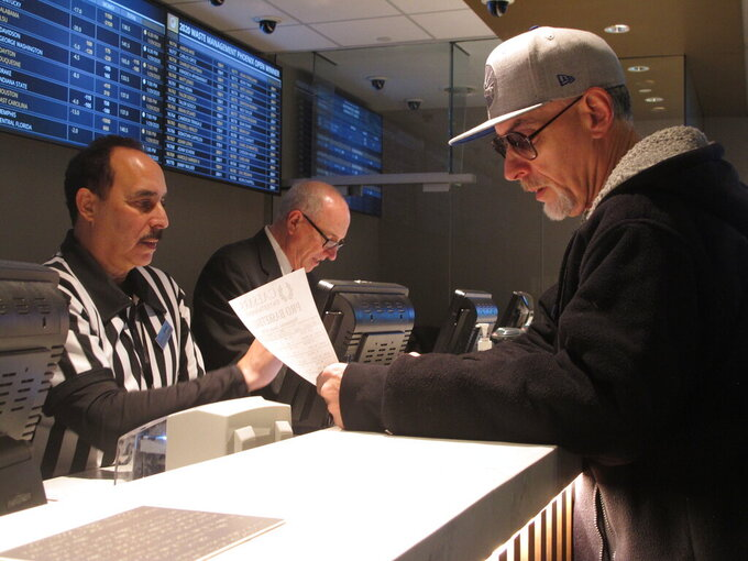 FILE - In this Jan. 29, 2020, file photo, a gambler makes bets on the Super Bowl at Bally's casino in Atlantic City, N.J. Sports books say the blitz of advertising they launched in the run up to the 2021 Super Bowl, while costly, paid off in terms of attracting new customers to the fast-growing legal sports betting industry in the U.S. (AP Photo/Wayne Parry)