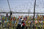 Visitors hang a ribbon on a wire fence decorated with other ribbons at the Imjingak Pavilion in Paju, South Korea, Tuesday, June 9, 2020. North Korea said Tuesday it will cut off all communication channels with South Korea as it escalates its pressure on the South for failing to stop activists from floating anti-Pyongyang leaflets across their tense border. (AP Photo/Lee Jin-man)