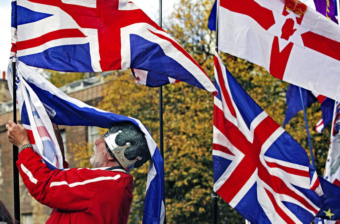 A man arranges Union flags and an Ulster Banner outside the Houses of Parliament on the day that Members of Parliament debated whether or not to hold a General Election to resolve the Brexit deadlock, in London, Tuesday, Oct. 29, 2019. Britain appeared on course Tuesday for an early general election that could break the country's political deadlock over Brexit, after the main opposition Labour Party said it would agree to the government's request to send voters to the polls in December. (Luciana Guerra/PA via AP)