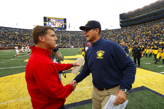 Rutgers head coach Chris Ash, left, and Michigan head coach Jim Harbaugh shake hands after an NCAA college football game in Ann Arbor, Mich., Saturday, Sept. 28, 2019. Michigan won 52-0. (AP Photo/Paul Sancya)