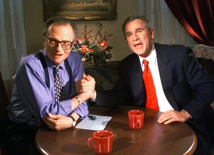FILE - In this Dec. 16, 1999 file photo, Republican presidential candidate Texas Gov. George W. Bush jokes with CNN's Larry King after finishing the