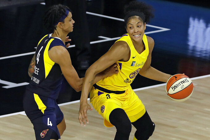 FILE - Los Angeles Sparks forward Candace Parker (3) goes to the basket against Indiana Fever forward Candice Dupree (4) during the first half of a WNBA basketball game in Bradenton, Fla., in this Wednesday, Aug. 5, 2020, file photo. The WNBA will tip off its 25th season on Friday, May 14, 2021, after an eventful offseason that was full of player movement, including Candace Parker returning home to Chicago. The former league MVP headed home after playing her entire 13-year career in Los Angeles since being drafted by the Sparks in 2008. (AP Photo/Chris O'Meara, File)