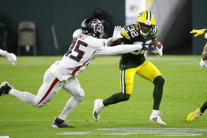 Green Bay Packers' Tyler Ervin (32) is tackled by Atlanta Falcons' Deion Jones (45) during the first half of an NFL football game, Monday, Oct. 5, 2020, in Green Bay, Wis. (AP Photo/Mike Roemer)