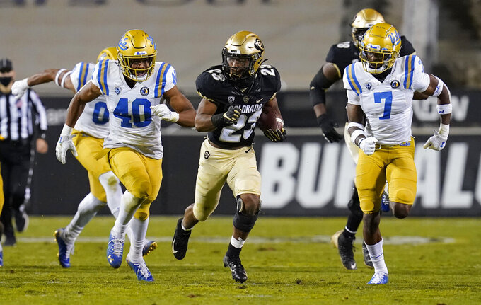 Colorado running back Jarek Broussard, center, slips between UCLA linebacker Caleb Johnson, left, and defensive back Mo Osling III for a long gain in the second half of an NCAA college football game Saturday, Nov. 7, 2020, in Boulder, Colo. (AP Photo/David Zalubowski)
