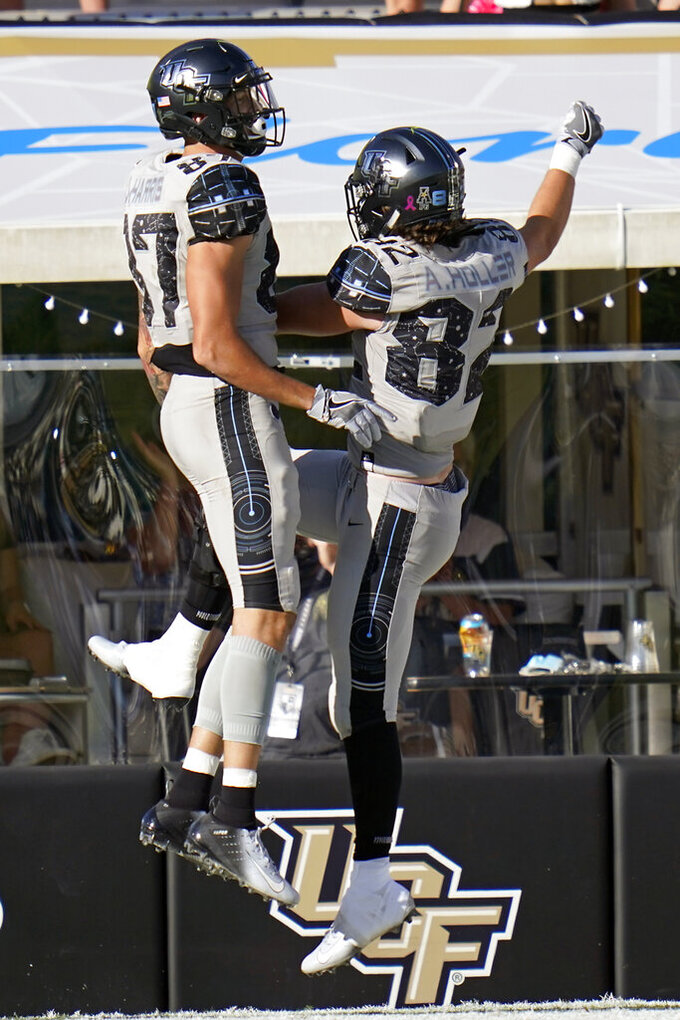 Central Florida wide receiver Jacob Harris, left, celebrates his touchdown reception against Tulane with teammate tight end Alec Holler (82) during the second half of an NCAA college football game Saturday, Oct. 24, 2020, in Orlando, Fla. (AP Photo/John Raoux)