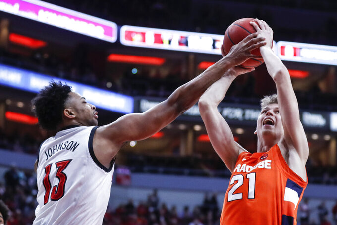 Syracuse forward Marek Dolezaj (21) is fouled by Louisville guard David Johnson (13) during the first half of an NCAA college basketball game Wednesday, Feb. 19, 2020, in Louisville, Ky. (AP Photo/Wade Payne)