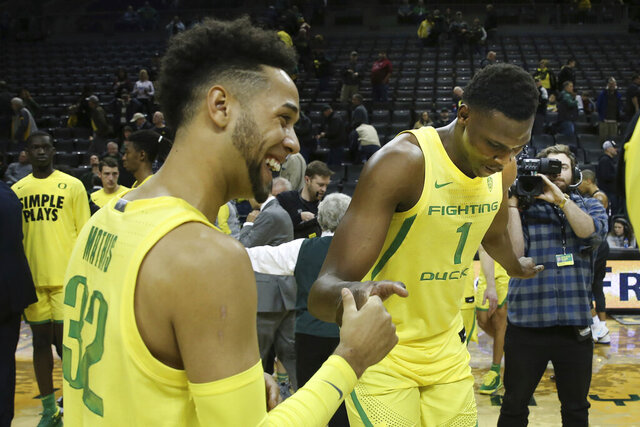 Oregon's Anthony Mathis, left, and N'Faly Dante celebrate after the team's 81-48 win over Montana during an NCAA college basketball game in Eugene, Ore., Wednesday, Dec. 18, 2019. (AP Photo/Chris Pietsch)