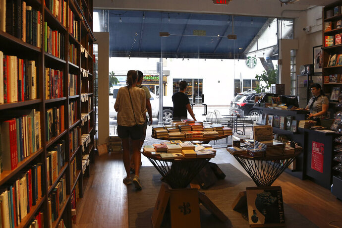 In this Nov. 6, 2019, photo, people shop at Books & Books, a locally owned business, in the Coconut Grove neighborhood in Miami. On Friday, Nov. 15, the Commerce Department releases U.S. retail sales data for October. (AP Photo/Lynne Sladky)
