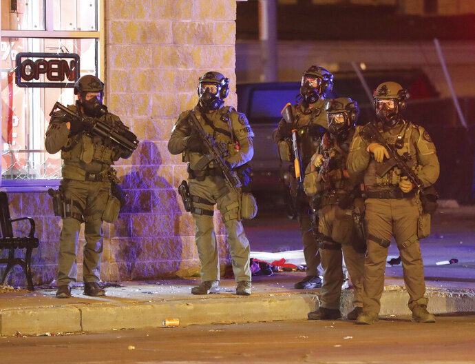 Officers in swat gear work at the intersection of West Fond du Lac Avenue and West Burleigh Street near a Jet Beauty store that was looted in Milwaukee on Sunday, May 31, 2020. (Mike De Sisti/Milwaukee Journal-Sentinel via AP)