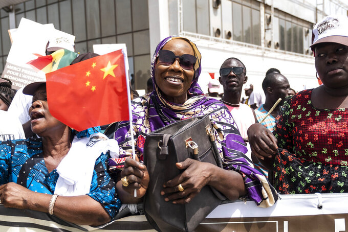 FILE - In this July. 21, 2018, file photo, a Senegal resident welcomes Chinese President Xi Jinping during his visit to Dakar, Senegal. China's loans to poor countries in Africa and Asia impose unusual secrecy and repayment terms that are hurting their ability to renegotiate debts after the coronavirus pandemic, a group of U.S. and German researchers said in a report Wednesday, March 31, 2021. (AP Photo/Xaume Olleros, File)