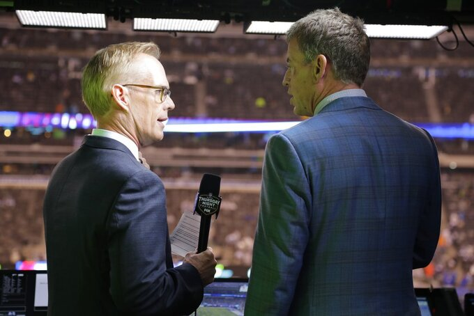 "FILE - This Oct. 11, 2018, file photo shows Troy Aikman, right, and Joe Buck working before an NFL football game between the New York Giants and the Philadelphia Eagles  in East Rutherford, N.J. ""I remember opening weekend when I got home I had a couple college buddies that were raving about the pregame show and how great and fun it was with everyone,"" said Aikman, who was Cowboys quarterback in 1994 before joining the network seven years later. ""It was refreshing, new and unique, and that set the tone for the network.""(AP Photo/Frank Franklin II, File)"
