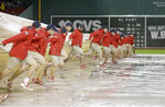 Fenway Park grounds crew workers remove a tarp from the field during a rain delay before a scheduled baseball game between the Oakland Athletics and the Boston Red Sox, Tuesday, May 15, 2018, in Boston. (AP Photo/Steven Senne)