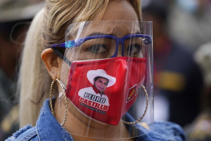 A supporter of presidential candidate Pedro Castillo wears a mask with an image of Castillo, during a march in Lima, Peru, Wednesday, June 9, 2021. Peruvians are still waiting to learn who will become their president next month as votes from Sunday's runoff election continued to be counted and the tiny difference between the two polarizing populist candidates narrowed. (AP Photo/Martin Mejia)