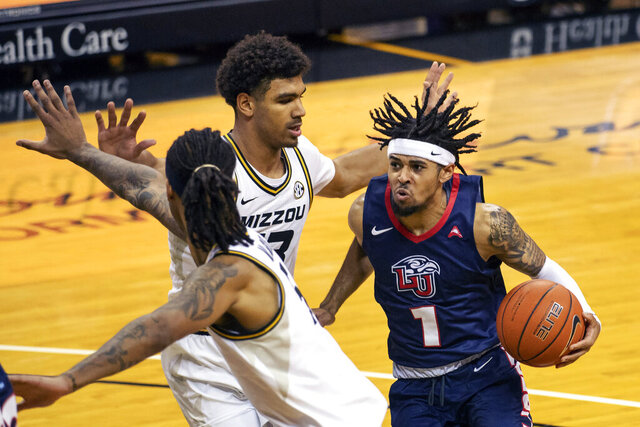 Liberty's Chris Parker, right, tries to drive past Missouri's Mark Smith, center, and Mitchell Smith during the first half of an NCAA college basketball game Wednesday, Dec. 9, 2020, in Columbia, Mo. Missouri won 69-60.(AP Photo/L.G. Patterson)
