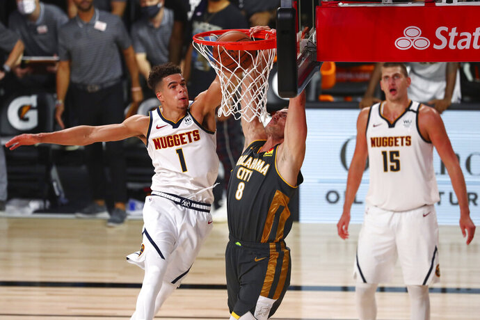 Oklahoma City Thunder forward Danilo Gallinari (8) dunks the ball against Denver Nuggets forward Michael Porter Jr. (1) during overtime in an NBA basketball game Monday, Aug. 3, 2020, in Lake Buena Vista, Fla. (Kim Klement/Pool Photo via AP)