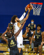 Michigan forward Isaiah Livers (2) goes to the basket while defended by Oakland forward Daniel Oladapo (4) in the first half of an NCAA college basketball game at Crisler Center in Ann Arbor, Mich., Sunday, Nov. 29, 2020. (AP Photo/Tony Ding)