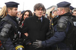 Police surround Catalonia's former regional president Carles Puigdemont, center right, and his wife Marcela Topor, center left, as he arrives at the European Parliament in Strasbourg, eastern France, Monday, Jan. 13, 2020. Puigdemont will attend his first session as a member of the European Parliament despite facing an arrest warrant against him in Spain. (AP Photo/Francisco Seco)