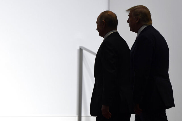 FILE - In this June 28, 2019, file photo, President Donald Trump and Russian President Vladimir Putin walk to participate in a group photo at the G20 summit in Osaka, Japan. An odd new front in the U.S.-Russian rivalry has emerged as a Russian military cargo plane bearing a load of urgently needed medical supplies landed in New York's JFK airport. (AP Photo/Susan Walsh, File)