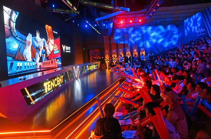Fans watch the match of the 2020 League of Legends World Championship televised on a screen at a Tencent V-station in Shanghai, China, Oct. 31, 2020. Hugely popular online games and celebrity culture are the latest targets in the ruling Communist Party's campaign to encourage China's public to align their lives with its political and economic goals. (Chinatopix Via AP)