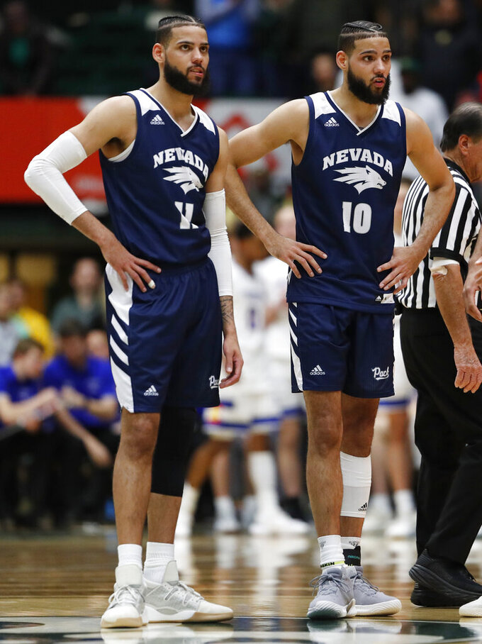 Nevada forwards Cody Martin, left, and Caleb Martin wait as a technical foul shot is taken in the second half of the team's NCAA college basketball game against Colorado State on Wednesday, Feb. 6, 2019, in Fort Collins, Colo. Nevada won 98-82. (AP Photo/David Zalubowski)