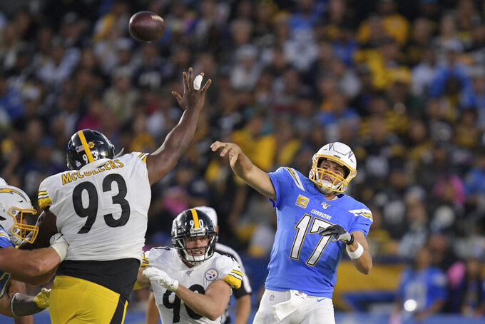 Los Angeles Chargers quarterback Philip Rivers, right, passes as Pittsburgh Steelers defensive tackle Dan McCullers-Sanders, left, and outside linebacker T.J. Watt defend during the first half of an NFL football game, Sunday, Oct. 13, 2019, in Carson, Calif. (AP Photo/Kyusung Gong)
