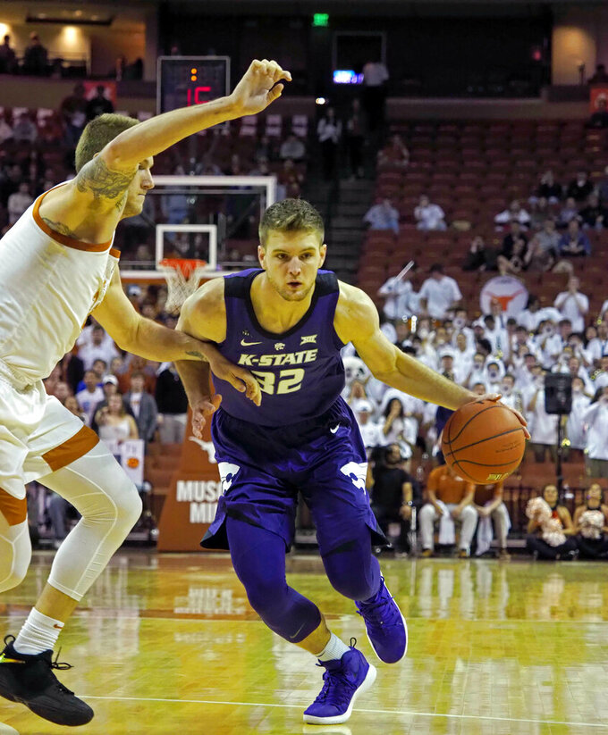 Kansas State forward Dean Wade, right, drives the ball against Texas forward Dylan Osetkowski, left, during the first half of an NCAA college basketball game, Tuesday, Feb. 12, 2019, in Austin, Texas. (AP Photo/Michael Thomas)
