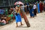 A man holds an oxygen tank while waiting outside the Naing oxygen factory at the South Dagon industrial zone in Yangon, Myanmar, Wednesday, July 28, 2021. Myanmar is currently reeling from soaring numbers of COVID-19 cases and deaths that are badly straining the country's medical infrastructure.  (AP Photo)