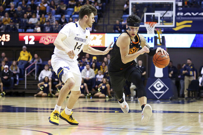Oklahoma State guard Lindy Waters III, right, is defended by West Virginia guard Chase Harler during the first half of an NCAA college basketball game Tuesday, Feb. 18, 2020, in Morgantown, W.Va. (AP Photo/Kathleen Batten)