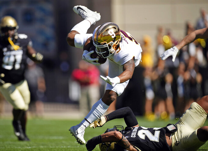 Colorado safety Isaiah Lewis, bottom, trips up Minnesota wide receiver Daniel Jackson after he pulled in a pass in the first half of an NCAA college football game Saturday, Sept. 18, 2021, in Boulder, Colo. (AP Photo/David Zalubowski)