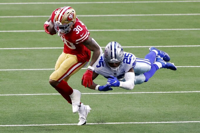 San Francisco 49ers running back Jeff Wilson Jr. (30) carries the ball for a short gain as Dallas Cowboys safety Xavier Woods (25) attempts to make the stop in the second half of an NFL football game in Arlington, Texas, Sunday, Dec. 20, 2020. (AP Photo/Michael Ainsworth)