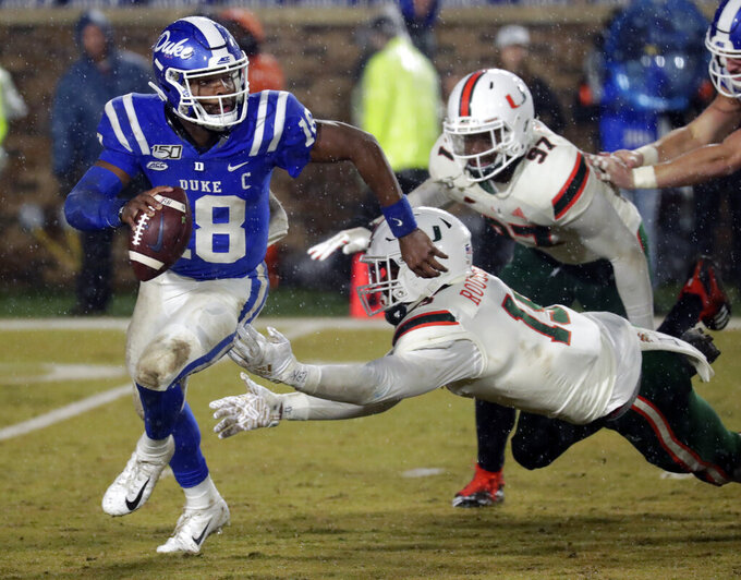 Duke's Quentin Harris (18) evades Miami's Gregory Rousseau (15) and Jonathan Garvin (97) during the fourth quarter of an NCAA college football game in Durham, N.C., Saturday, Nov. 30, 2019. (AP Photo/Chris Seward)