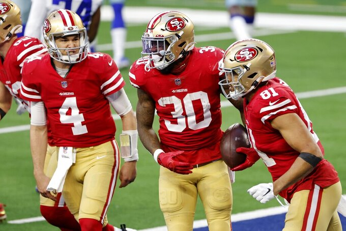 San Francisco 49ers' Nick Mullens (4), Jeff Wilson Jr. (30) and Jordan Reed (81) celebrate a touchdown scored by Wilson in the second half of an NFL football game against the Dallas Cowboys in Arlington, Texas, Sunday, Dec. 20, 2020. (AP Photo/Michael Ainsworth)