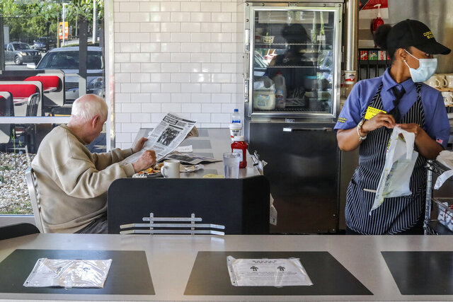 Waffle House's Tiffany, right, get To Go orders ready as a seated guest enjoys his meal on Monday, April 27, 2020, at The Waffle House in Brookhaven, Ga. Restaurants around metro Atlanta began to reopen dining rooms as restrictions related to the coronavirus pandemic are lifted. (John Spink/Atlanta Journal-Constitution via AP)