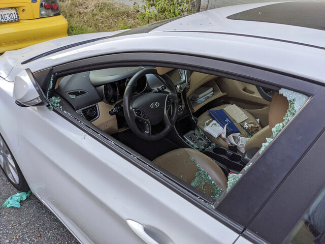 This Thursday, May 21, 2020, photo shows a parked car with a broken driver's side window after a smash-and-grab break-in in Los Angeles. The coronavirus hasn't been kind to car owners. With more people than ever staying home to lessen the spread of COVID-19, their sedans, pickup trucks and SUVs are parked unattended on the streets, making them easy targets for opportunistic thieves.  (AP Photo/Damian Dovarganes)