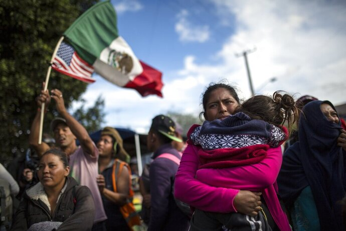 FILE - In this Nov. 22, 2018 file photo, Honduran migrant Leticia Nunes holds her daughter Mailyn amid a small group of migrants trying to make their way to the U.S. as Mexican police in riot gear block them from the Chaparral border crossing in Tijuana, Mexico. U.S. ambassadors from El Salvador, Honduras and Haiti sent urgent cables, made public Thursday, Nov. 7, 2019, to the White House in the early days of the Trump administration, pleading with them to abandon plans to send hundreds of thousands of migrants back to their home countries. (AP Photo/Rodrigo Abd, File)
